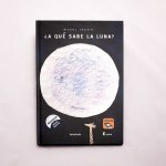 """Vista superior del libro """"¿A qué sabe la luna?"""" [Descripción de imagen]. En portada, la ilustración de una luna llena. Bajo la luna, una pequeña jirafa."""