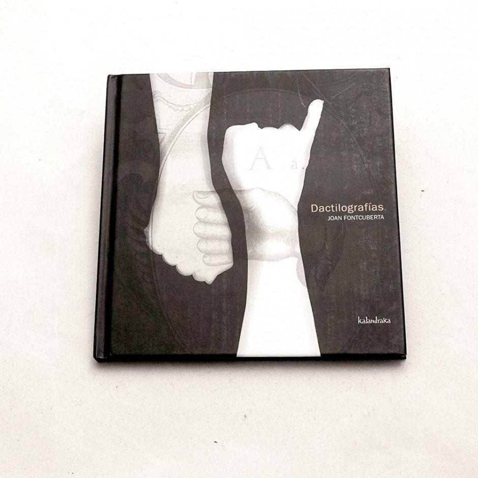 """Vista superior del lLibro """"Dactilografías"""". [Descripción de imagen] En portada, una ilustración de tres manos con diferente opacidad articulando letras del alfabeto dactilológico."""