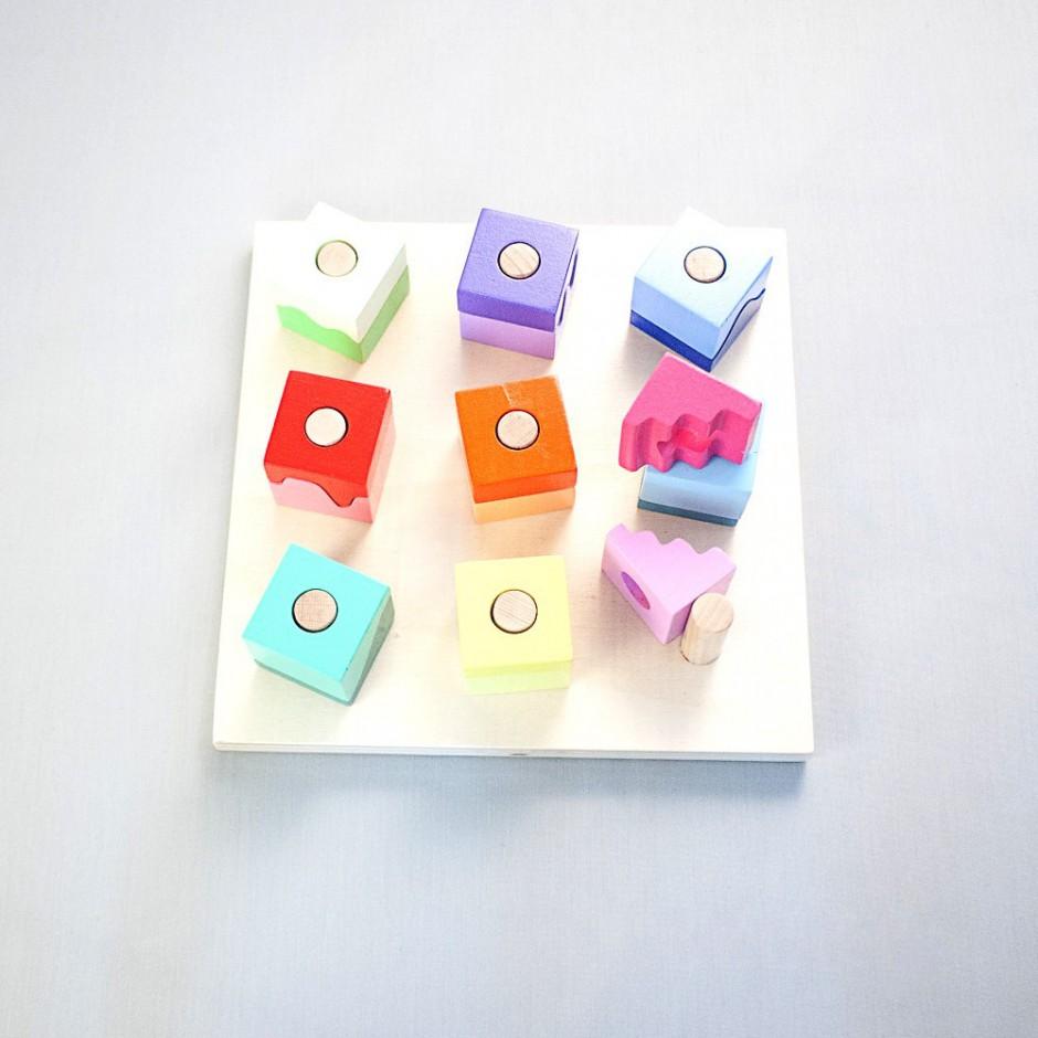"""Detalle del puzle """"Pasteles"""". [Descripción de imagen] Ocho piezas completas insertadas en los pivotes de la base del puzle. En la esquina inferior derecha, dos semipiezas desencajadas."""