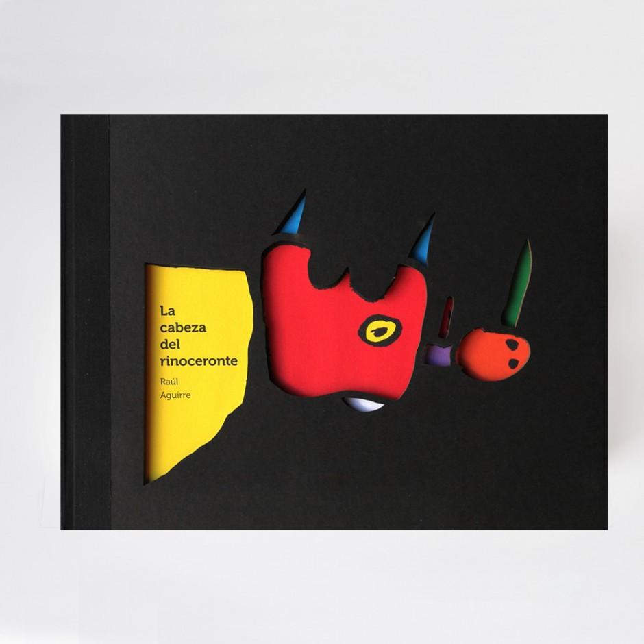 """Vista superior del libro """"La cabeza del Rinoceronte"""". [Descripción de imagen] En portada, la ilustración en relieve de la cabeza de un rinoceronte. A ambos lados de la cabeza, dos ilustraciones abstractas."""