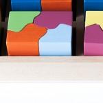 """Detalle del puzle """"6x4"""". [Descripción de imagen] Varias piezas completas de diferente color encajadas en la base del puzle."""