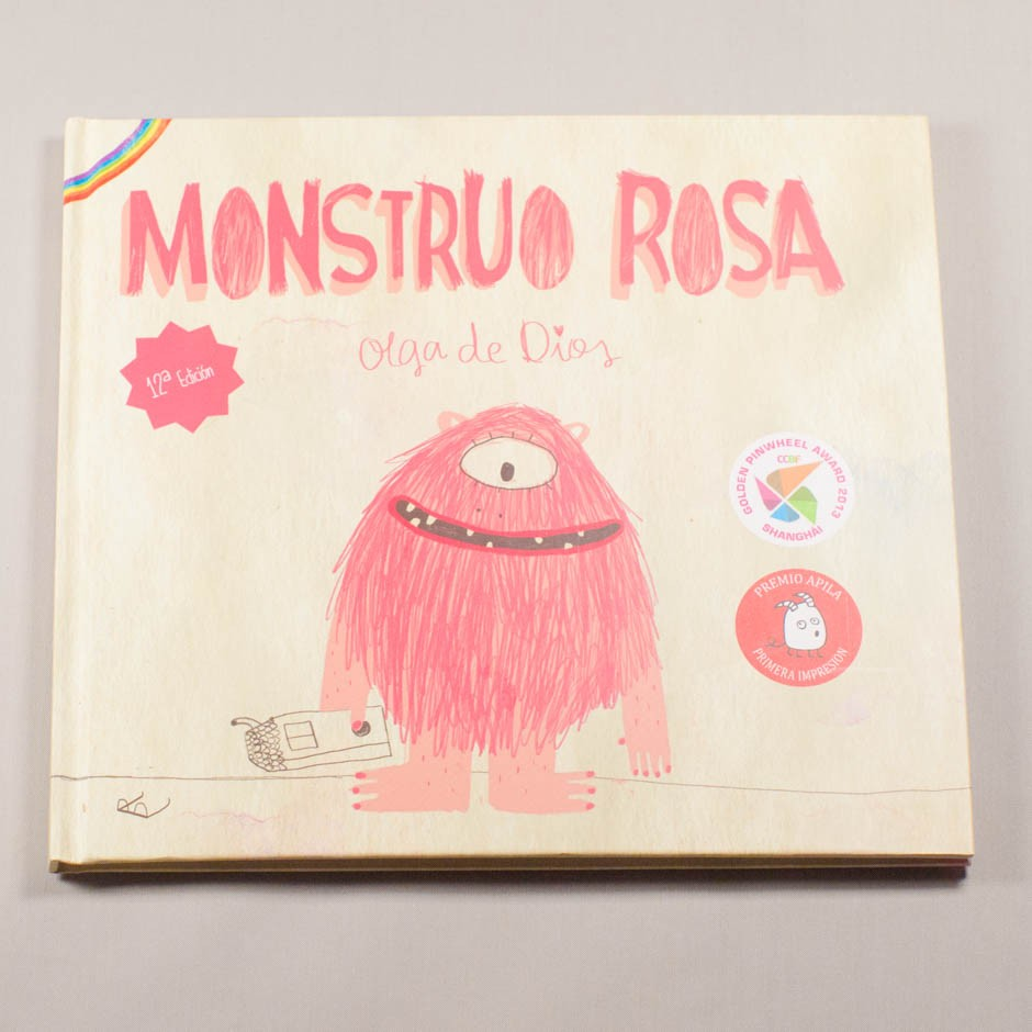 """Libro """"Monstruo Rosa"""". En portada, un monstruo peludo, sonriendo, con un solo ojo y un juguete en la mano."""
