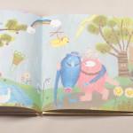 """Detalle del libro """"Monstruo Rosa"""". [Descripción de imagen] Páginas internas. De izquierda a derecha, el monstruo rosa abrazado a un monstruo azul en un bosque con árboles, un lago, flores y diferentes animales."""