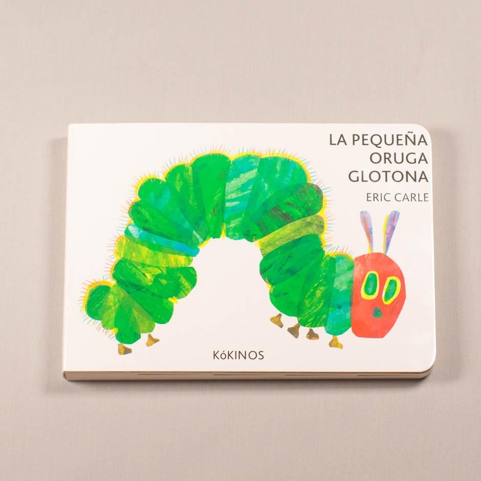 """Libro """"La pequeña oruga glotona"""". En portada, la ilustración de una oruga con rostro y seis patas."""