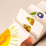"""Detalle del libro """"La pequeña oruga glotona"""". [Descripción de imagen] Páginas internas. De izquierda a derecha. Un sol de colores, una manzana, dos peras de colores y una ciruela, entre otras figuras."""