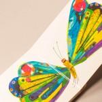 """Detalle del libro """"La pequeña oruga glotona"""". [Descripción de imagen] Páginas internas. De izquierda a derecha, una gran mariposa de colores con las alas desplegadas."""