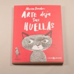 """Vista superior del libro """"Arte deja tus huellas"""". [Descripción de imagen] En portada, un gato y un pájaro realizados con huellas dactilares."""