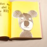 """Vista superior del libro """"Arte deja tus huellas"""". [Descripción de imagen] Páginas internas. A la derecha, un oso realizado con huellas dactilares."""