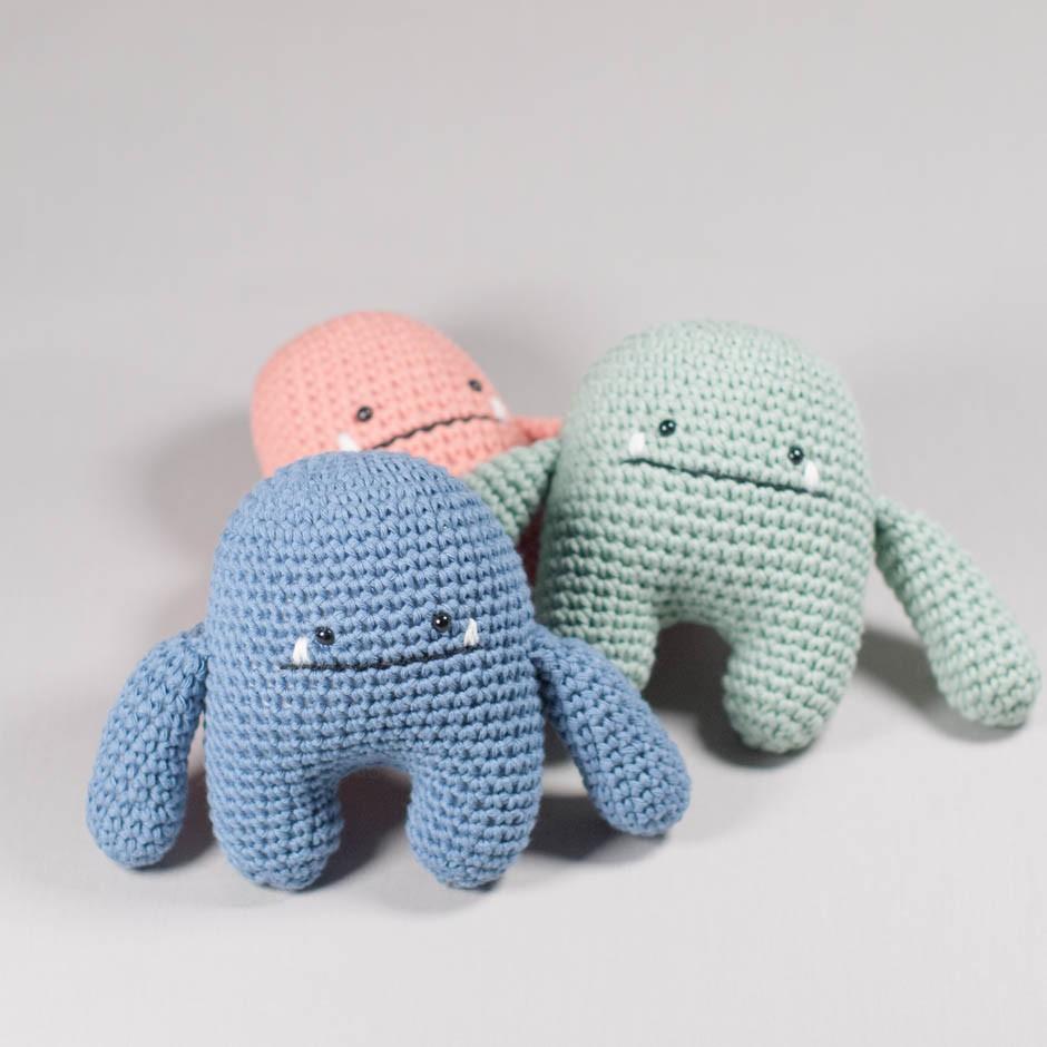 Vista frontal de tres muñecos Cucu en diferentes colores realizados en croché.