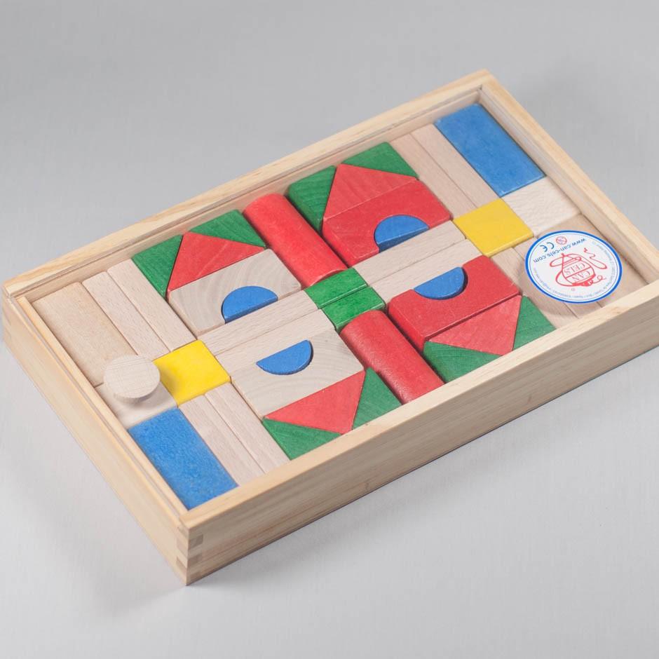 """Vista superior del puzle """"Arquitecturas"""". [Descripción de imagen] Varias piezas de diferentes formas y colores colocadas en la caja."""
