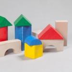 """Detalle del puzzle """"Arquitecturas"""". [Descripción de imagen] Diez piezas triangulares, circulares y cuadradas colocadas, una sobre otra, formando casas."""