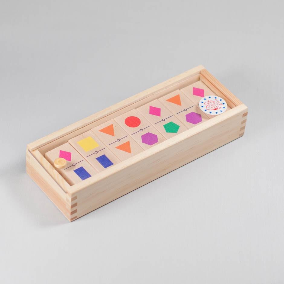 """Vista superior del juego """"Dominó"""". [Descripción de imagen] Varias piezas de madera con diferentes formas geométricas dibujadas sobre ellas colocadas en la caja."""