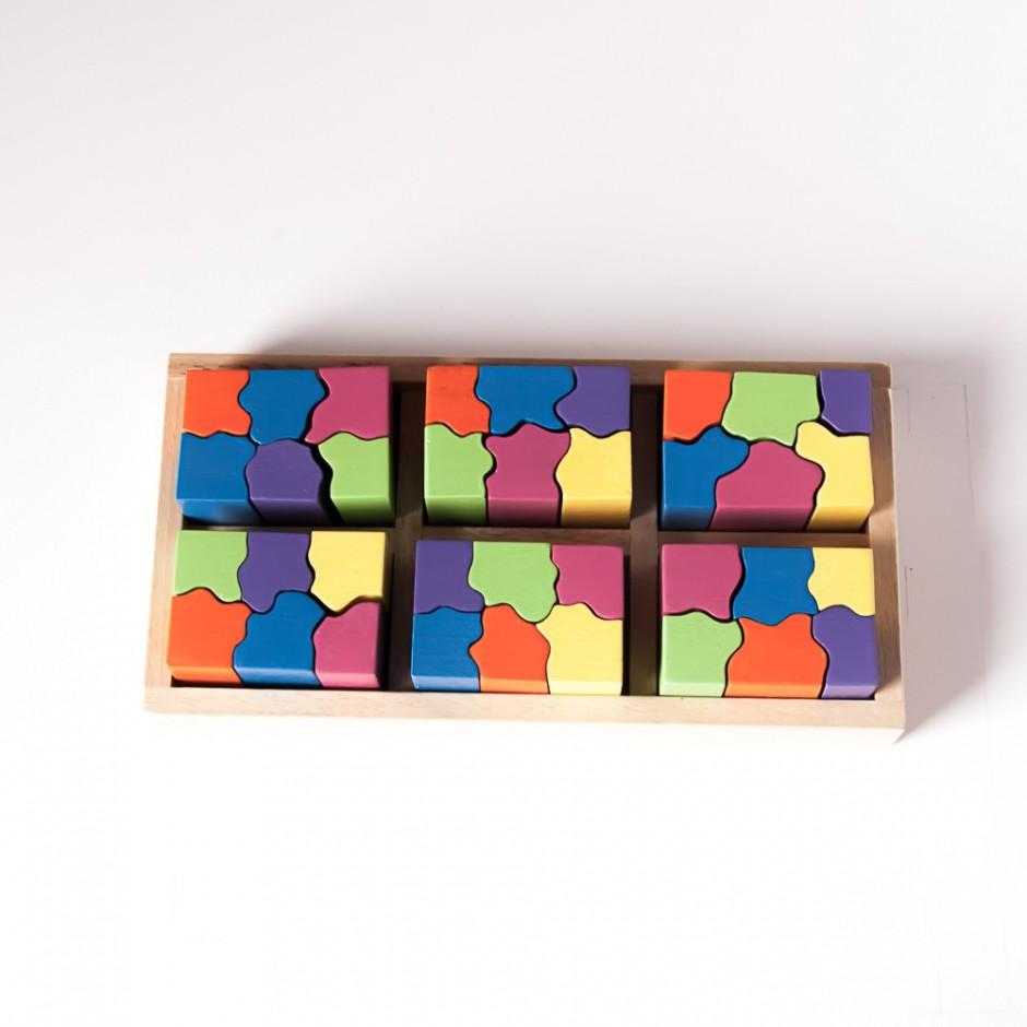 """Vista superior del puzle """"6x6"""". [Descripción de imagen] Seis piezas completas de diferente color encajadas en la base del puzle. Las piezas completas están formadas por seis semipiezas."""