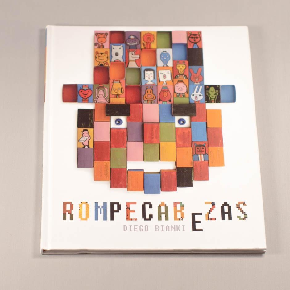 """Libro """"Rompecabezas"""". En portada, un puzzle en forma de rostro, compuesto de piezas de colores con rostros dibujados."""