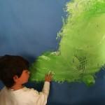 Vista posterior de un niño pintando con su manos trazos verdes sobre papel un papel azul en una Propuesta de experimentación de la obra The River.