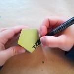 Detalle de dos manos infantiles firmando con rotulador una pieza de madera coloreada con pintura acrílica amarilla.