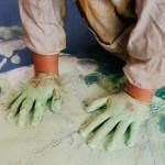 Vista superior de dos manos infantiles cubiertas de pintura verde, pintando sobre una lona azul en el suelo.