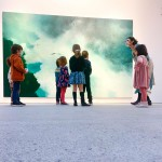 Vista lateral de un grupo de siete niños atentos a María, mientras ésta les habla frente a la obra The River, de Hugo Fontanela.