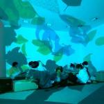 Vista lateral de siete niños, sentados en una habitación con imágenes proyectadas en las paredes, pintando cajas concentrados en el suelo.