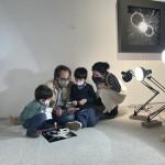 Fotografía. Vista lateral de María en el suelo de una sala de exposición, acompañada de un hombre y dos niños. Iluminados por varias lámparas, realizan manualidades.