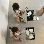 Fotografía. Vista superior de dos niñas sentadas en el suelo realizando manualidades con los materiales de Arte en Familia. Entre ellos, papel, tijeras y un láser LED.