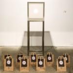 Fotografía. Vista frontal de una escultura del artista Pablo Armesto. Bajo esta, una decena de bolsas de papel de Cazapeonzas con el material necesario para la nueva sesión de Arte en Familia.