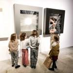 Fotografía. Vista lateral de Maria junto a cuatro niñas a las que explica las dos esculturas de Armesto colgadas en la pared.