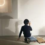 Fotografía. Vista posterior de un niño proyecto en la pared la escultura en papel que ha realizado. A su izquierda, un cuadro de Armesto.