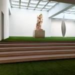 Fotografía. Vista general de una sala expositiva. En primer plano, unas escaleras separan al observador de la escultura de madera del fondo.
