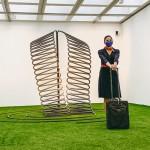 Fotografía. Vista frontal de la escultura de hierro 'Alfaguara' (M. Chirino). Junto a ella, María posando con una maleta.