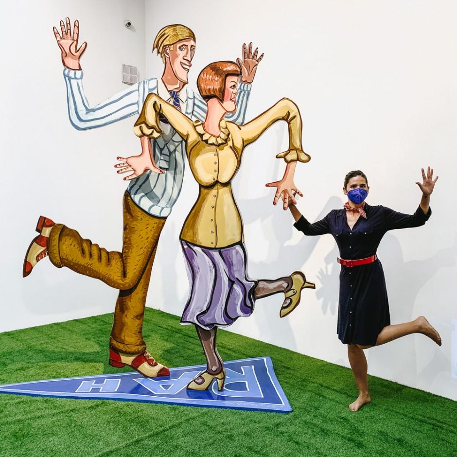 Fotografía. Esculturas de aluminio (Red Grooms) representando a dos personas bailando el charlestón. Junto a ellas, María bailando.