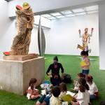 Vista lateral de un grupo de niños y niñas junto a María, haciendo manualidades, sentados en el suelo bajo la escultura 'Hera half'.