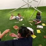 Dos niños frente a María haciendo manualidades mientras atienden. Sentado y estirado en el suelo, respectivamente, bajo la escultura 'Able Charlie'.