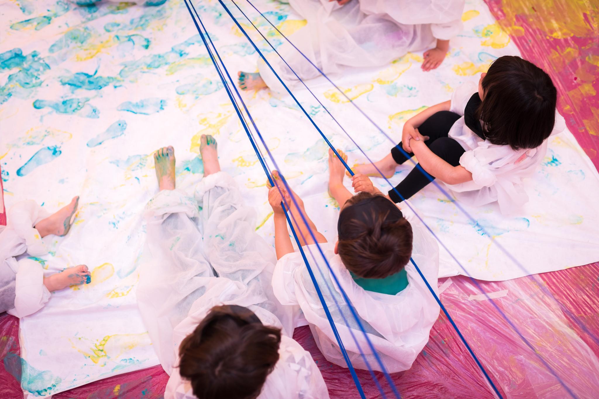 Vista superior de cuatro niñas y niños sentados sobre una tela pintada, tensando cuerdas sobre esta.