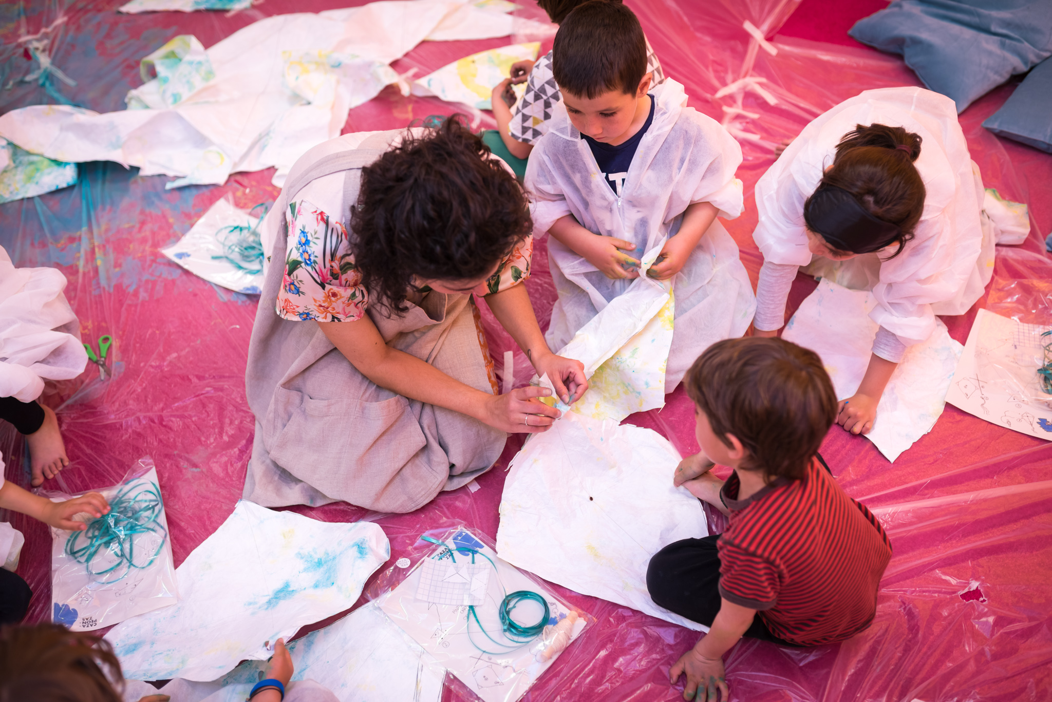 Vista superior de un grupo de niñas y ninos que, junto a María, realizan manualidades con tela y pintura.