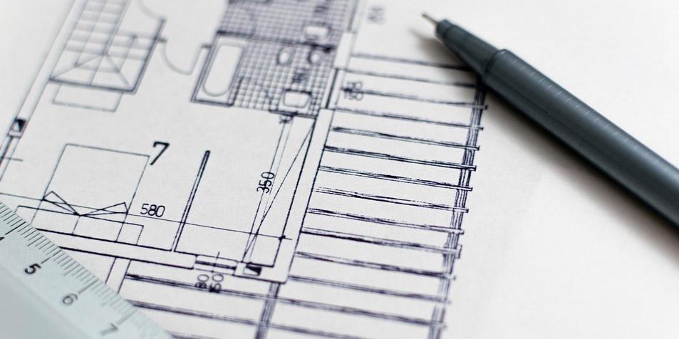 Sobre un plano arquitectónico de una construcción, una regla graduada y un lápiz.