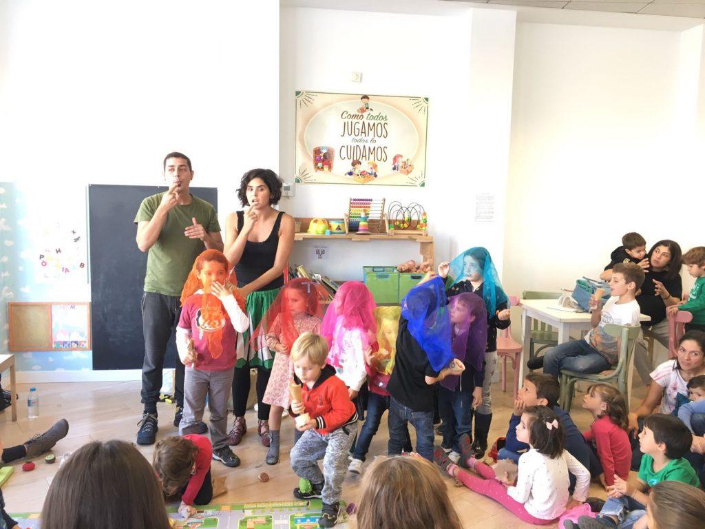 """Instantánea del cuentacuentos """"Para gustos, los colores"""". [Descripción de imagen] María y un compañero intérprete de lengua de signos narran el cuento frente a un grupo de niñas, niños y madres en una sala con juguetes infantiles."""