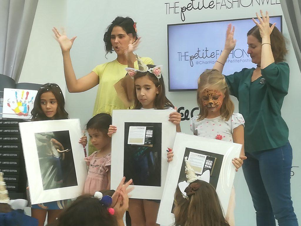 """Instantánea del cuentacuentos """"Colores"""",  en la Galería de Cristal. [Descripción de imagen] María y Sara están en el escenario aplaudiendo en lengua de signos junto a cuatro niñas que muestran unas láminas con ilustraciones."""
