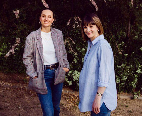 Fotografía de las fundadoras de Recién Mamá, en un entorno ajardinado. Ambas sonríen.
