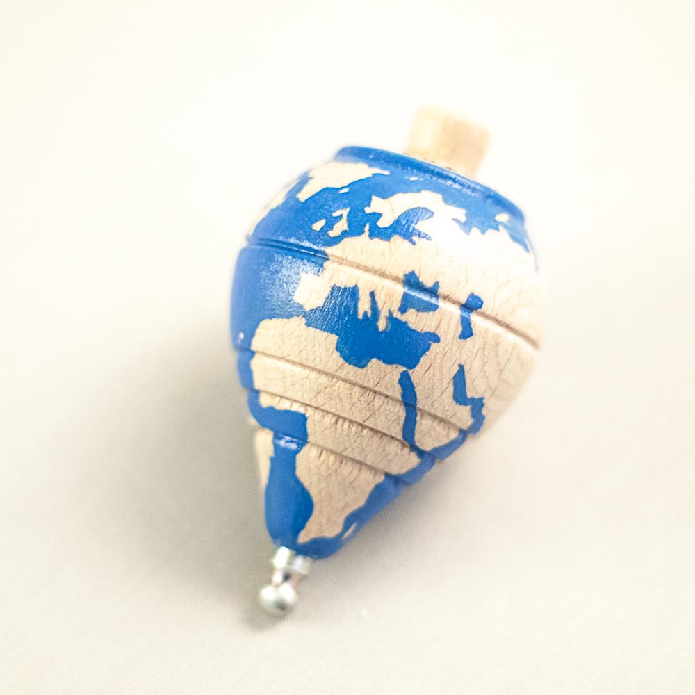Vista superior de una peonza de madera con un mapa del mundo dibujado en ella.
