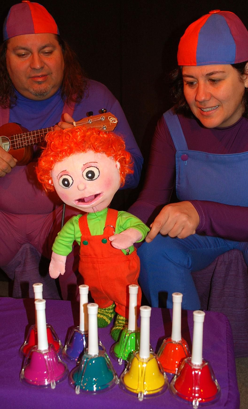 Pareja vestida con un peto azul y un gorro. A la izquierda un señor con ukelele y a la derecha una señora con marioneta de niño. Delante de ellos varias campanas.