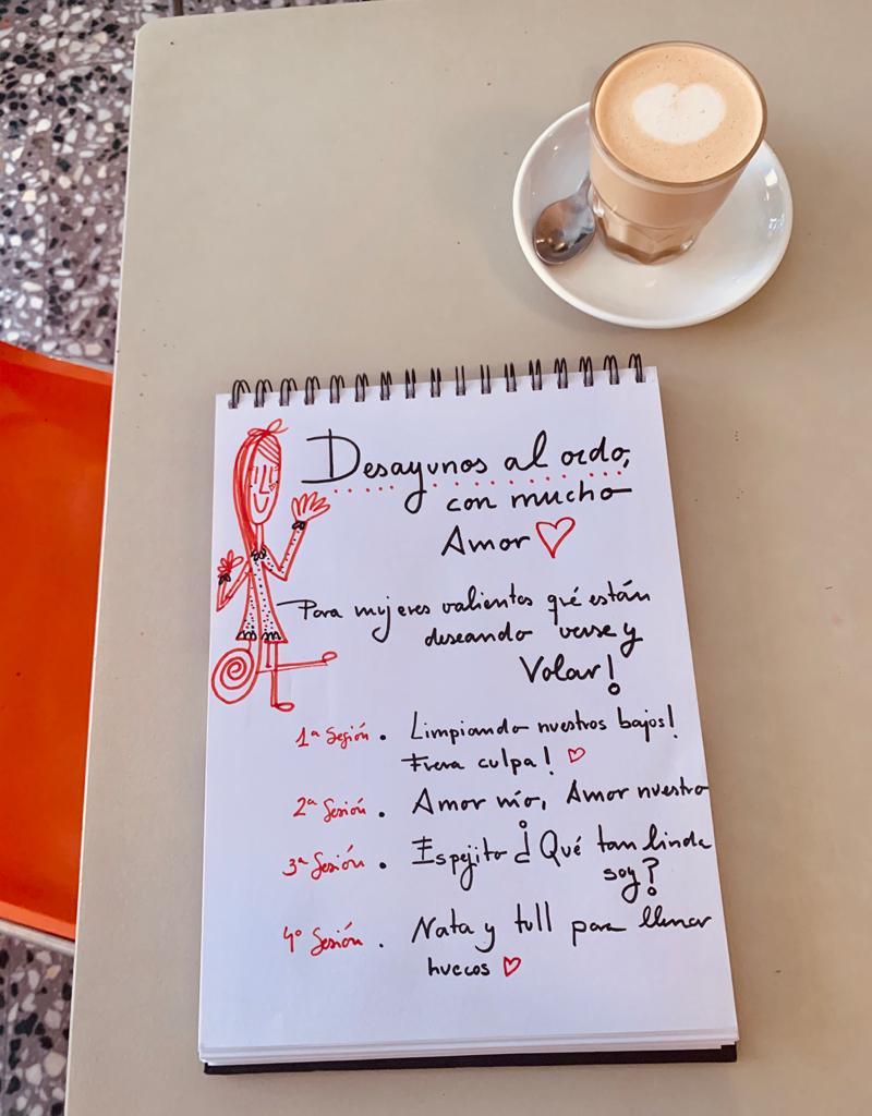 Vista superior de un cuaderno escrito y un café. [Transcripción del texto] Desayunos al oído con mucho amor. Para mujeres valientes que están deseando verse y volar. 1 sesión:Limpiando nuestros bajos. Fuera culpas. Segunda sesión: Amor mío, amor nuestro. Tercera sesión: Espejito, ¿qué tan linda soy?  Cuarta sesión: Nata y tull para llenar huecos.