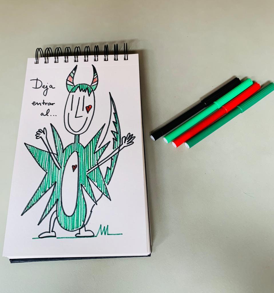Vista superior de un cuaderno con un dibujo de dragón y varios rotuladores.