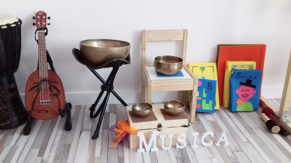 Visión frontal de varios instrumentos musicales. [Descripción de imagen] De izquierda a derecha: un tambor, tres cuencos de diferentes tamaños, una silla y varios cuadros.