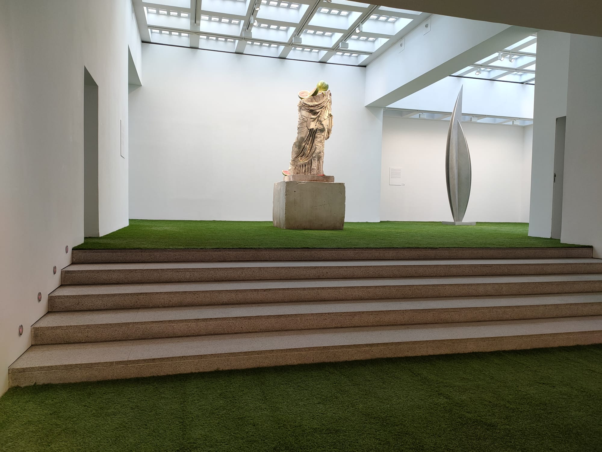 Vista interior de la escalera central de la galería. En la parte de arriba se ven dos esculturas de la exposición.