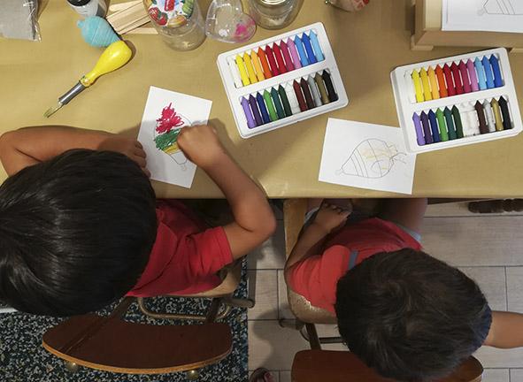 Dos niños pintando en una mesa