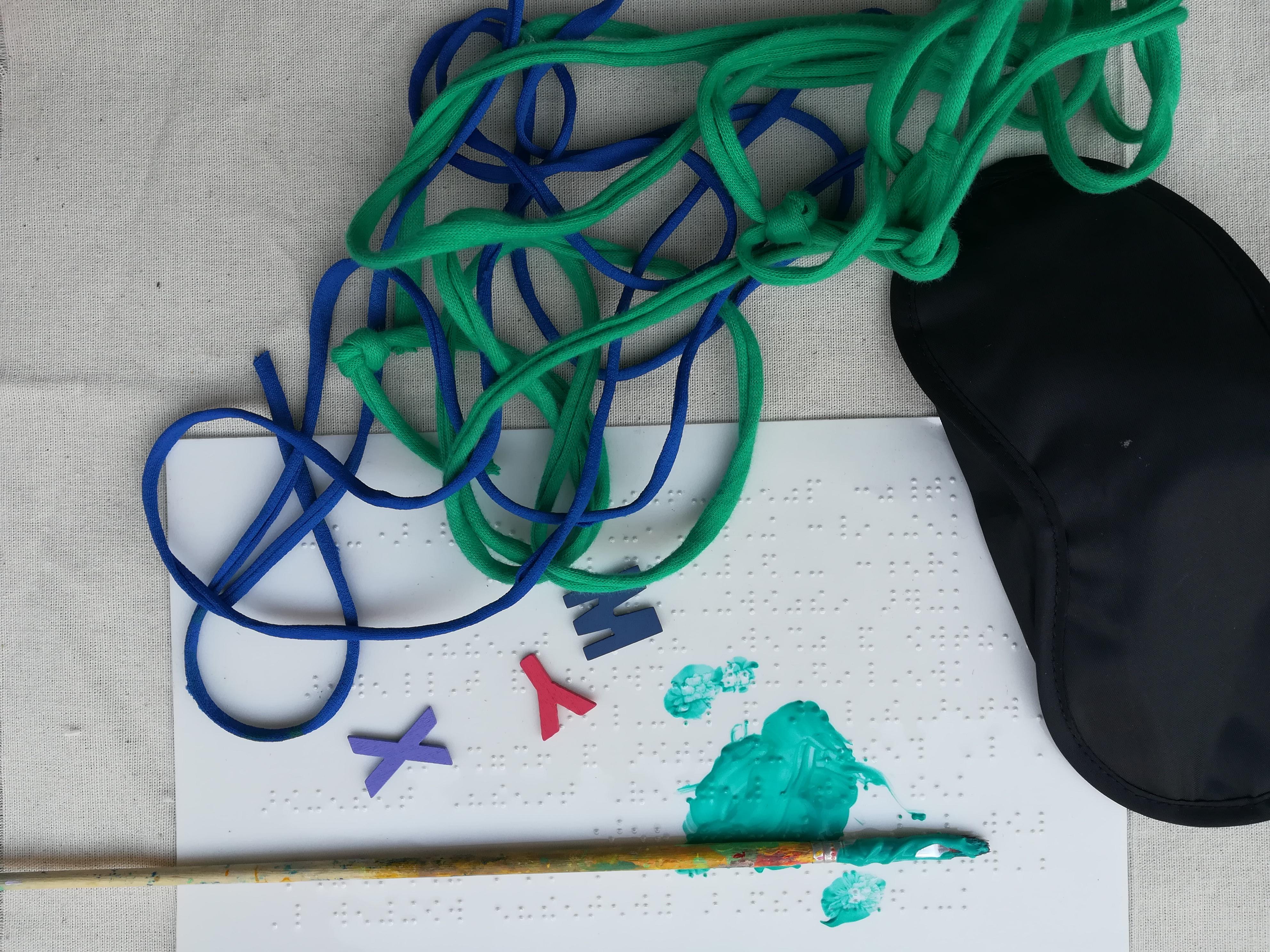 Vista superior de un globo, cuerdas de colores, un pincel y un papel con acuarelas.
