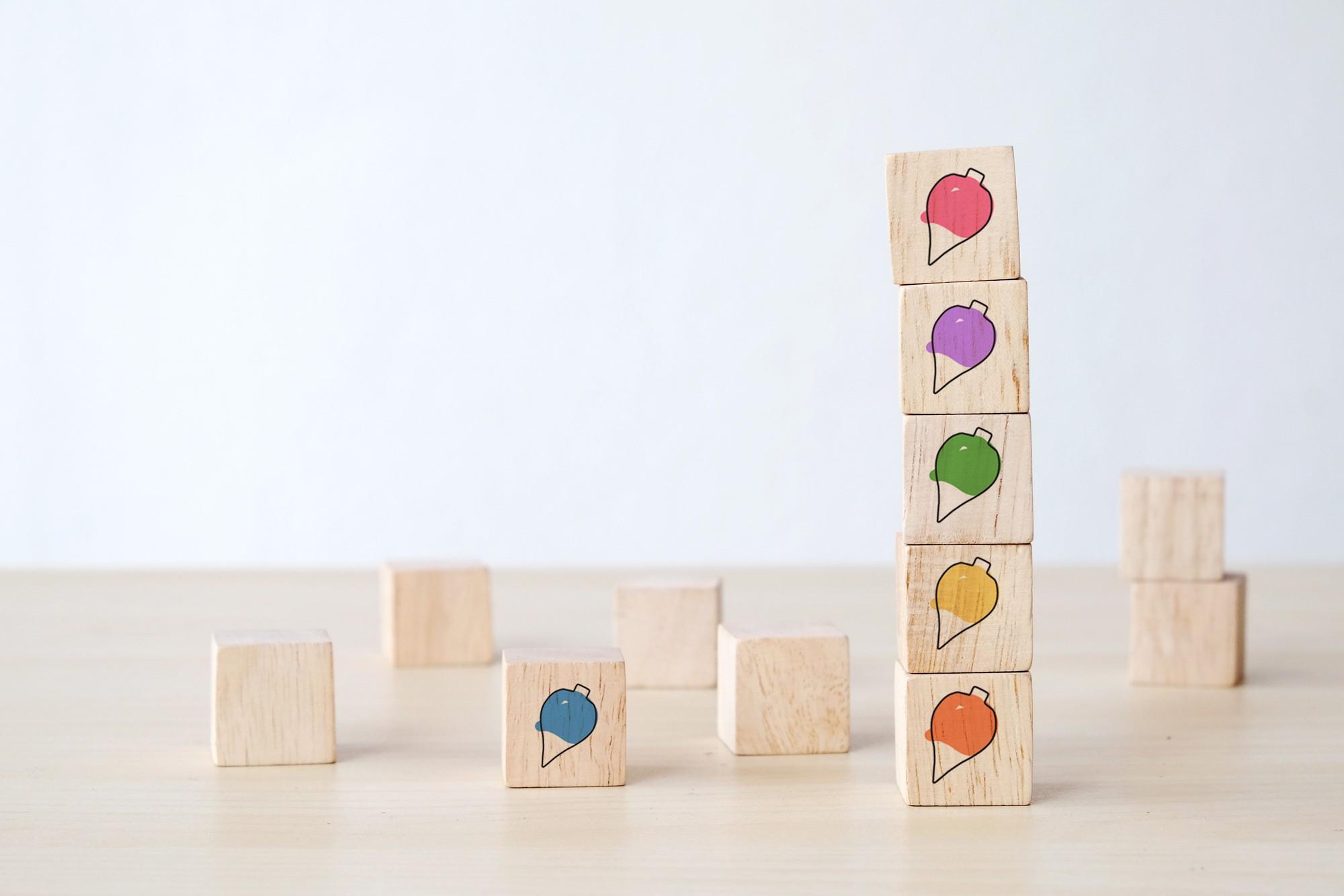 Doce piezas de madera en forma de cubo esparcidas sobre una mesa. Seis de ellas con una peonza dibujada.