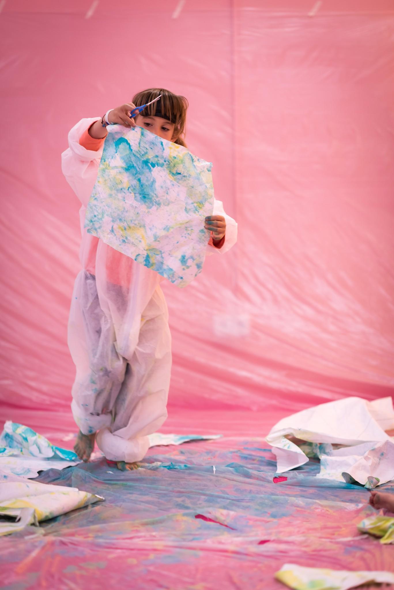 Vista frontal de una niña, con un mono desechable, sosteniendo un pequeño lienzo pintado con acuarela.